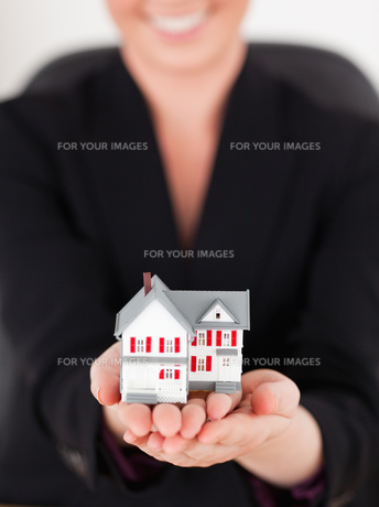 Young attractive redhaired woman in suit holding a miniature houseの写真素材 [FYI00484334]
