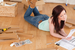 Beautiful redhaired girl reading a manual before do-it-yourself while lying on the floorの素材 [FYI00484337]