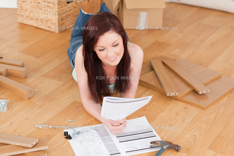 Pretty redhaired girl reading a manual before do-it-yourself while lying on the floorの素材 [FYI00484339]
