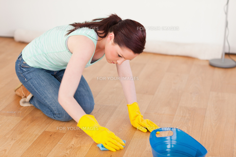 Gorgeous redhaired woman cleaning the floor while kneelingの写真素材 [FYI00484342]