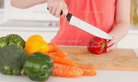 Woman cutting some vegetables in the kitchenの写真素材 [FYI00484345]