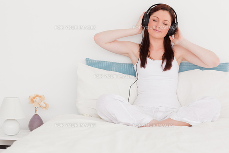 Gorgeous redhaired woman listening to music with her headphones while sitting on her bedの写真素材 [FYI00484351]