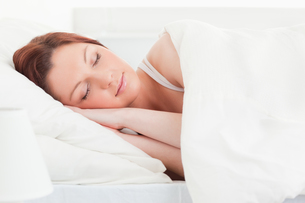 Close up of a good looking redhaired woman sleeping in her bedの写真素材 [FYI00484355]