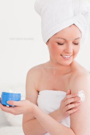 Cute young woman wearing a towel using skin creamの素材 [FYI00484364]