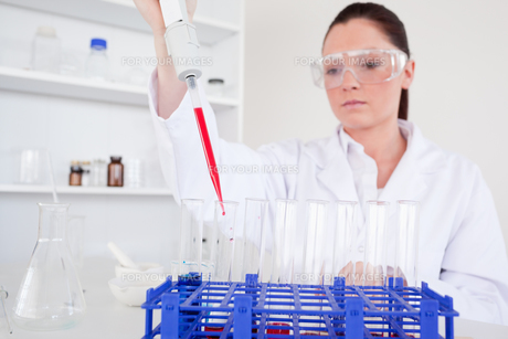 Pretty female biologist holding a manual pipette with sample from test tubesの写真素材 [FYI00484366]