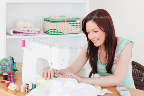 Pretty redhaired female using a sewing machineの素材 [FYI00484370]
