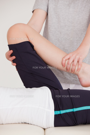 Portrait of a masseuse stretching the leg of a youn womanの写真素材 [FYI00484386]