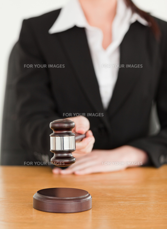 Young woman using a gavel while sitting at a deskの写真素材 [FYI00484394]