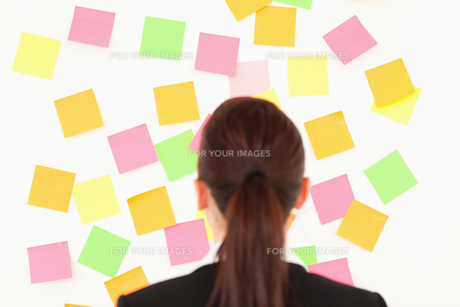 Redhaired woman looking at a wall full of repositional notesの素材 [FYI00484395]