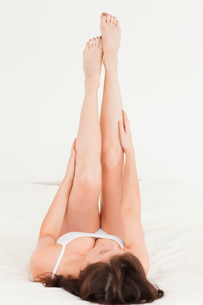 Beautiful brunette female stretching her legs while lyingの写真素材 [FYI00484405]