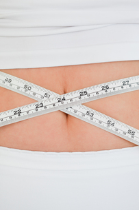 Young woman measuring her belly with a tape measure while standingの写真素材 [FYI00484406]
