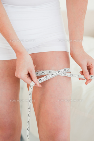 Young woman measuring her hip with a tape measure while standingの写真素材 [FYI00484407]