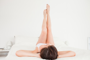 Attractive brunette female stretching her legs while lyingの素材 [FYI00484408]