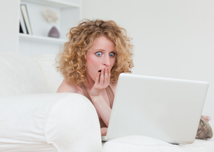 Beautiful surprised female relaxing with her laptop while sitting on a sofaの写真素材 [FYI00484413]