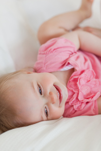 Cute blond baby lying on a bedの写真素材 [FYI00484418]