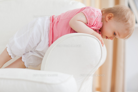 Cute blond baby standing on a sofaの写真素材 [FYI00484420]