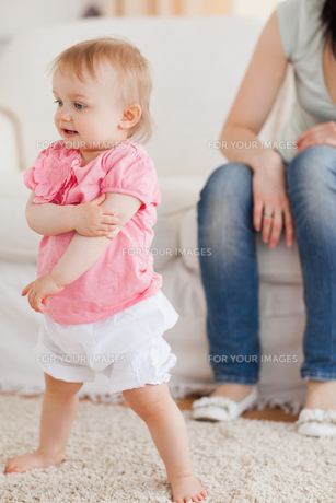 Baby standing on a carpet while her mother is sitting on a sofaの写真素材 [FYI00484421]