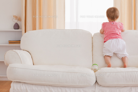 Blond baby standing on a sofaの写真素材 [FYI00484422]