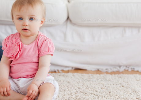 Lovely blond baby looking at the camera while sitting on a carpetの素材 [FYI00484423]