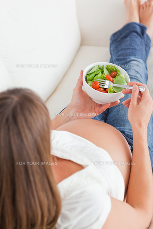 Good looking pregnant woman eating a salad while lying on a sofaの写真素材 [FYI00484432]