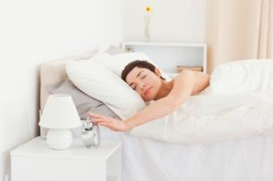 Cute woman turning off her alarm clockの写真素材 [FYI00484443]