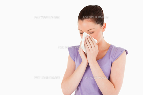 Good looking woman sneezing while standingの写真素材 [FYI00484454]
