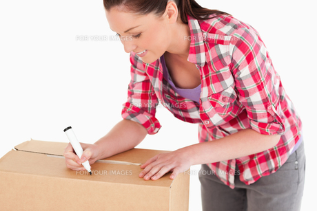 Portrait of a beautiful woman writing on cardboard boxes with a marker while standingの素材 [FYI00484458]