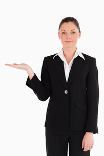Attractive woman in suit showing a copy space while standingの写真素材 [FYI00484459]