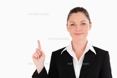 Good looking woman in suit pointing at a copy spaceの写真素材 [FYI00484461]