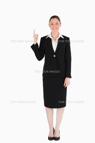 Good looking female in suit pointing at a copy spaceの写真素材 [FYI00484464]