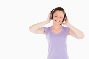 Pretty woman posing with headphones while standingの写真素材 [FYI00484472]