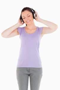 Gorgeous woman posing with headphones while standingの写真素材 [FYI00484474]