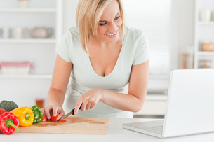 Woman enjoying cooking looking for a recipe on the laptopの素材 [FYI00484484]