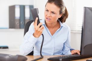 Upset businesswoman in officeの写真素材 [FYI00484488]