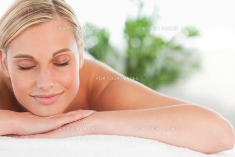 Close up of a blonde smiling woman relaxing on a lounger with eyes closedの素材 [FYI00484494]