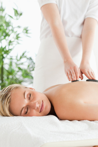 Blonde woman relaxing on a massage lounger during stone therapyの写真素材 [FYI00484495]