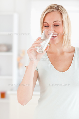 Smiling woman drinking waterの写真素材 [FYI00484496]