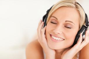 Close up of a serene woman wearing headphonesの写真素材 [FYI00484510]