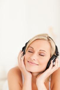 Portrait of a serene woman wearing headphonesの写真素材 [FYI00484516]