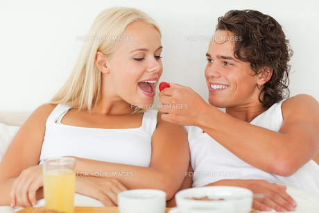 Handsome man giving a strawberry to his girlfriendの写真素材 [FYI00484520]