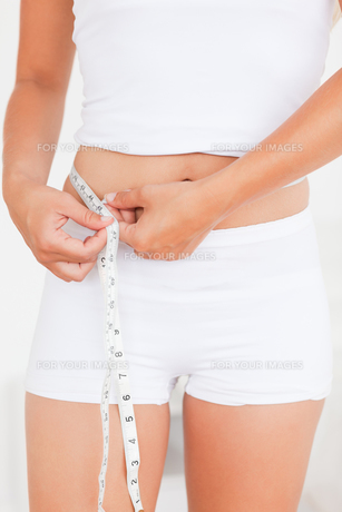 Woman measuring her bellyの写真素材 [FYI00484545]
