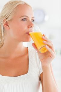 Portrait of a blonde woman drinking juiceの写真素材 [FYI00484550]