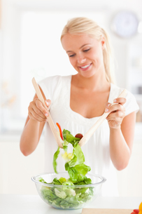 Portrait of a smiling woman mixing a saladの写真素材 [FYI00484551]