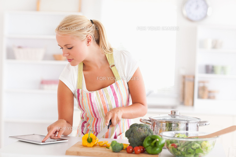 Blonde woman using a tablet computer to cookの写真素材 [FYI00484554]