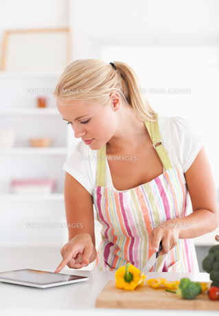 Portrait of a woman using a tablet computer to cookの写真素材 [FYI00484558]