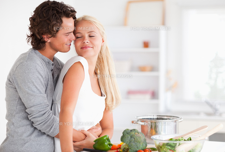 Cute couple hugging while cookingの写真素材 [FYI00484567]