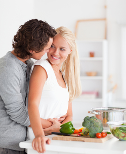 Portrait of a couple hugging while cookingの写真素材 [FYI00484568]