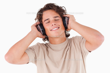 Smiling man with headphones having eyes closedの写真素材 [FYI00484577]