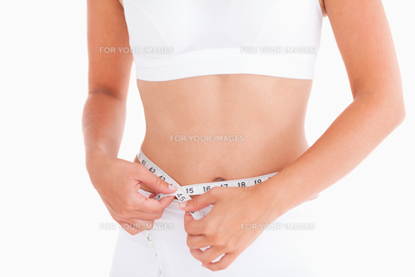 Thin woman measuring her waistの写真素材 [FYI00484584]