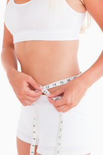 Fit woman measuring her waistの写真素材 [FYI00484586]